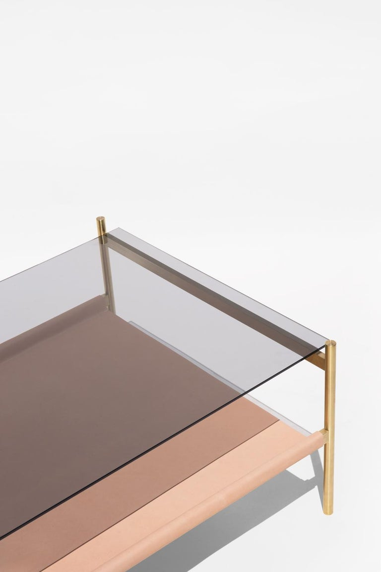 Made to order. Please allow 6 weeks for production.  Brass Frame / Smoked Glass / Natural Leather Sling  The Duotone Furniture series is based on a modular hardware system that pairs sturdy construction with visual lightness and a range of potential