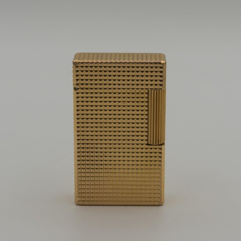 Stylish yellow gold-plated S. T. Dupont Ligne 1 gas lighter in large diamond cut finish, circa 1975. Marked on the base 'S.T Dupont, Paris, made in France, with plating thickness stamp (20 microns thick), serial no. and the ST Dupont makers mark. In