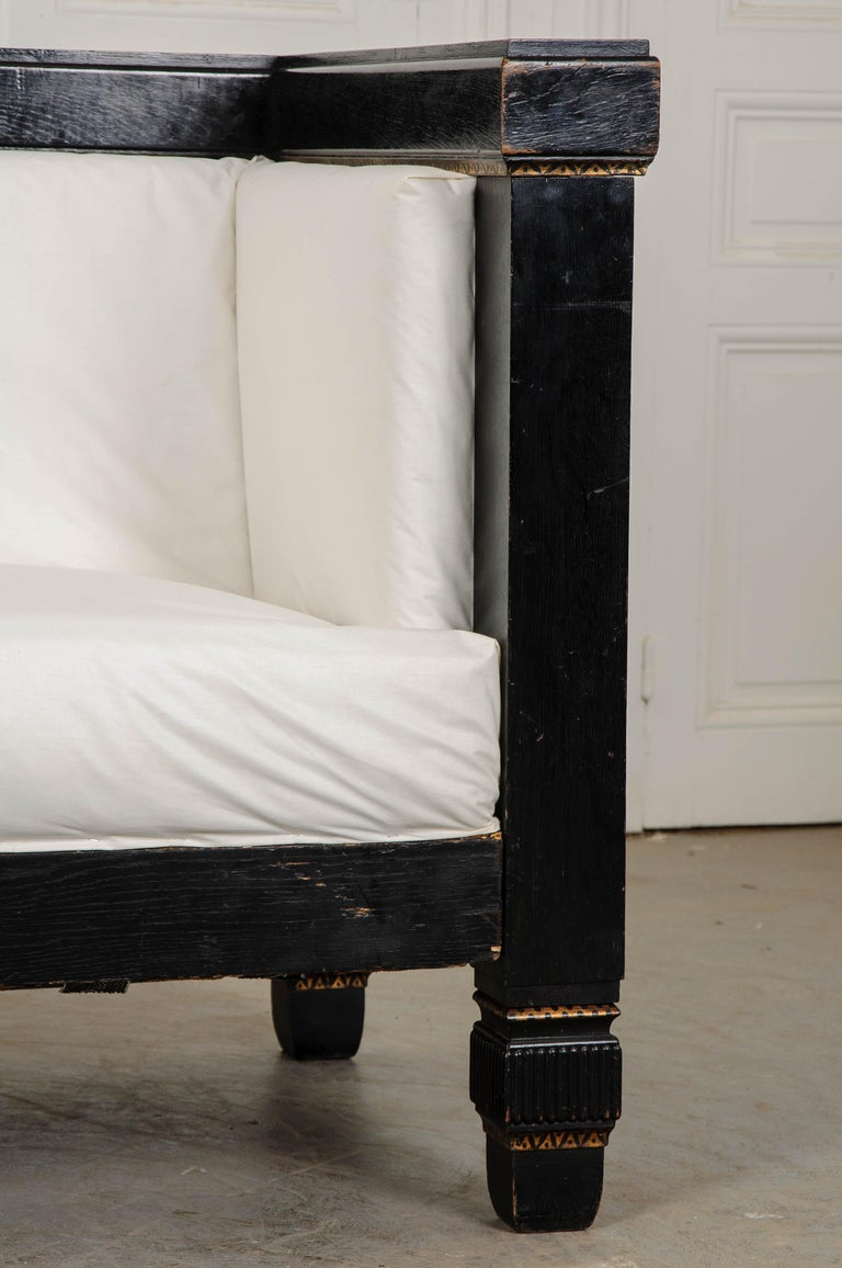This stunning ebonized and parcel-gilt Baroque-style box sofa, circa 1830s, is a great example of the Dutch Baroque style. The playful hand painted gold highlights against the black-lacquered wood and the coffered sides of square section emphasize