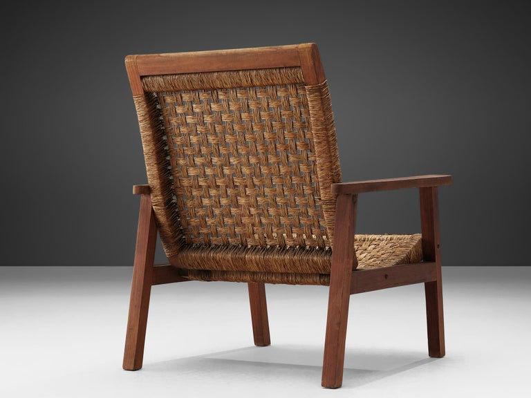Armchair, stained wood and woven rope, Netherlands, 1940s.  This lounge chair is executed in wood and rope. The design of this chair is minimalistic in a puritan way. The woven seat and backrest are simplistic, but give the sitter a comfortable