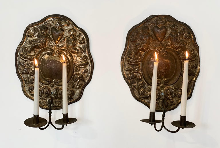 Pair of Dutch Baroque double-arm sconces, origin: Holland, circa 1760, silver plate repoussé.  Two candle arms with back plates decorated with centre cartouche surrounded by cherubs / putti, foliage and charming hearts.   We also sell bespoke,