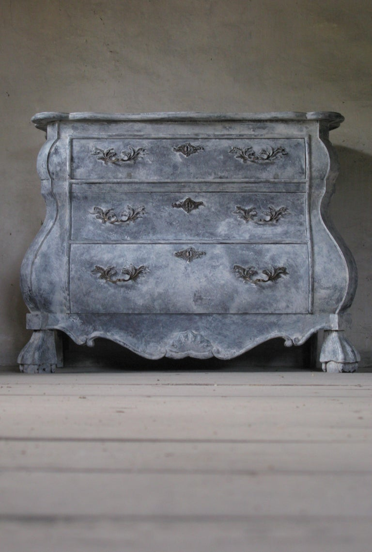 A Baroque style Dutch painted wood bombé three-drawer commode from my home country  This commode was born in the Netherlands and features a shaped top with beveled edges over three drawers, the upper one being smaller than the lower two. These