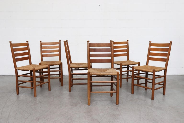 Quaker style dining chairs with rush seats, oak frames from an Old Church, Zuiderkerk, in Enkhuizen, Holland. Some have treated wormwood frames with visible holes that add to their overall aged look. A few retain the Bible shelf under the seat. All
