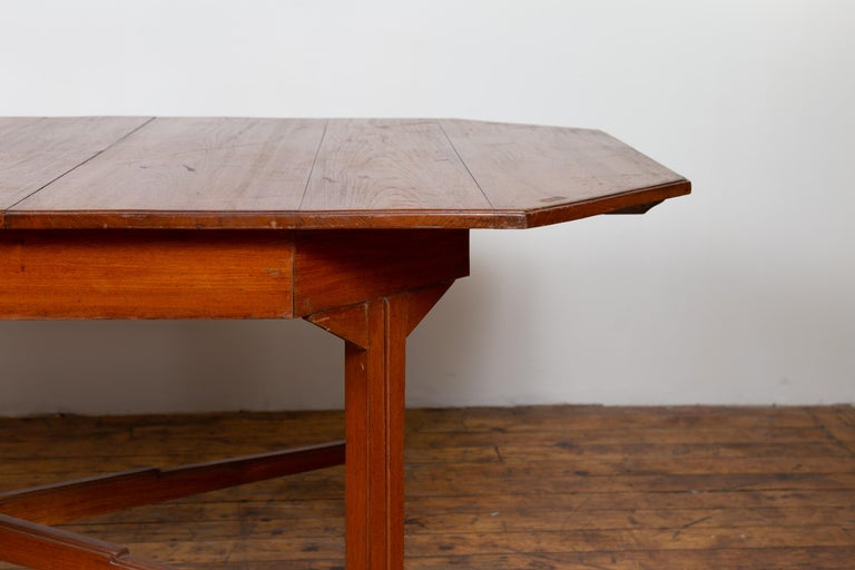An antique Dutch Colonial period Javanese extension dining table from the early 20th century, with canted corners and folding leaf. Born on the island of Java during the early years of the 20th century, this handsome dining table features a