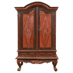 Dutch Colonial Late 19th Century Bonnet Top Cabinet with Carved Doors and Apron