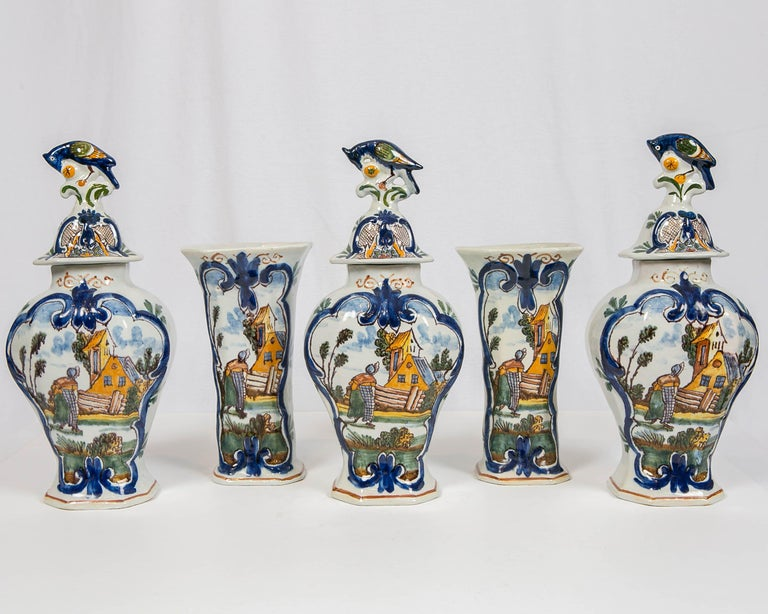 A five piece mantle garniture comprising three covered vases and a pair of beakers. Made in the Netherlands circa 1750 the vases are each hand painted on the front with a brightly colored, polychrome scene showing a Dutch peasant woman returning