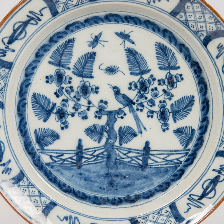 We are pleased to present this 18th century Dutch delft Blue and White charger made circa 1770. It is decorated with a garden scene showing a song bird perched in a flowering tree with butterflies flying above the garden.