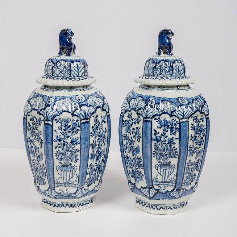 We are pleased to offer this beautiful pair of Dutch delft blue and white ginger jars with lion finials. They are molded in the traditional delft octagonal shape with a fluted surface. The jars are decorated with panels showing a songbird in a