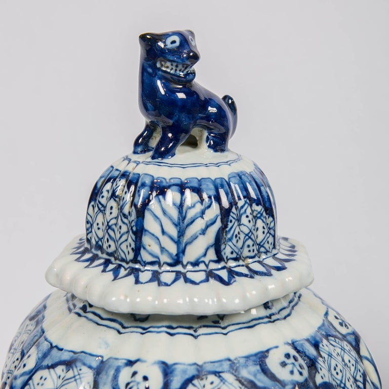 Hand-Painted Dutch Delft Blue and White Jars with Lion Finials Made For Sale