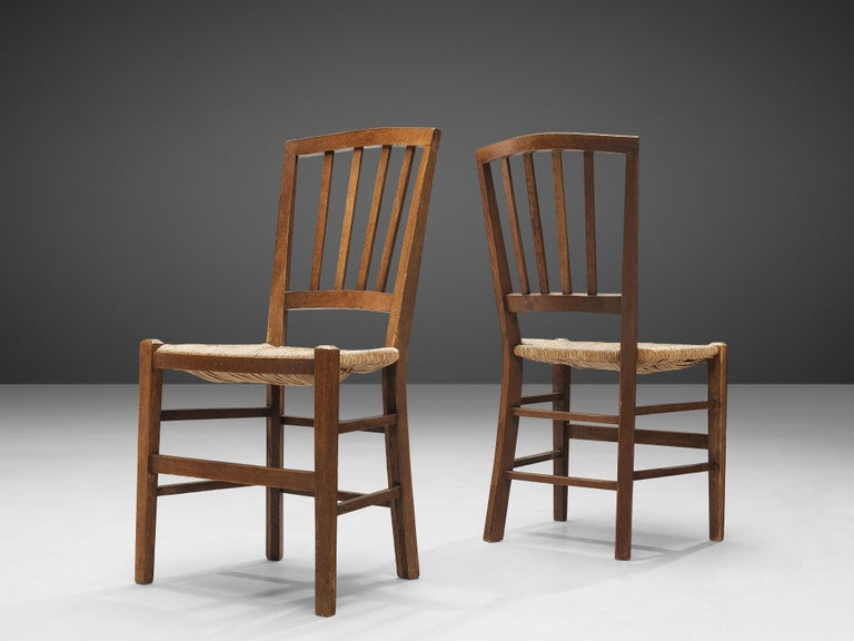 Dining chairs, oak, paper cord, the Netherlands, 1960s  These dining chairs feature a geometric backrest that slightly curves to provide comfort for the user. Vertical slats structure the backrest and create an airy as well as rhythmic look. With