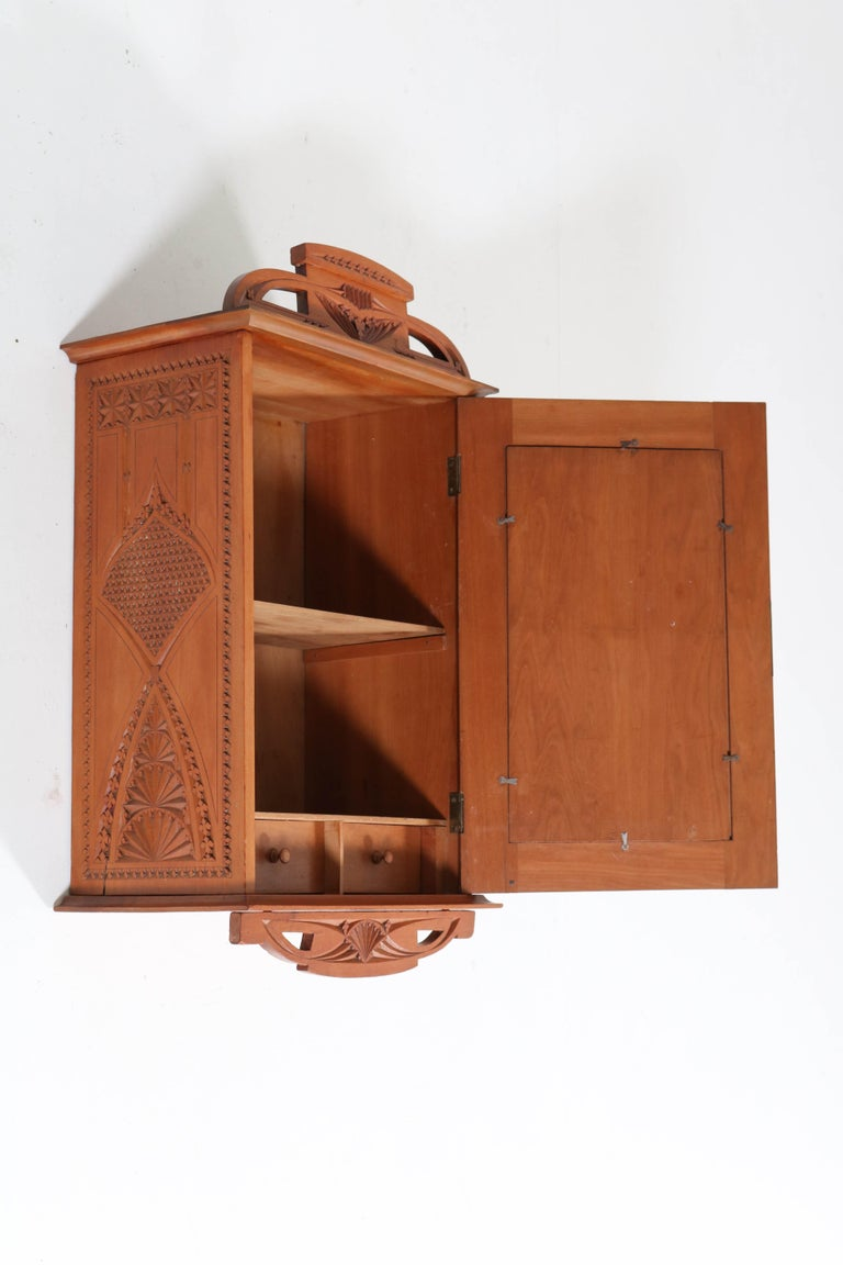 Offered by Amsterdam Modernism: Stunning and rare Art Nouveau wall cabinet. Fruitwood with nice kerfschnitt carving. Striking Dutch design from the 1900s. In good original condition with minor wear consistent with age and use, preserving a beautiful