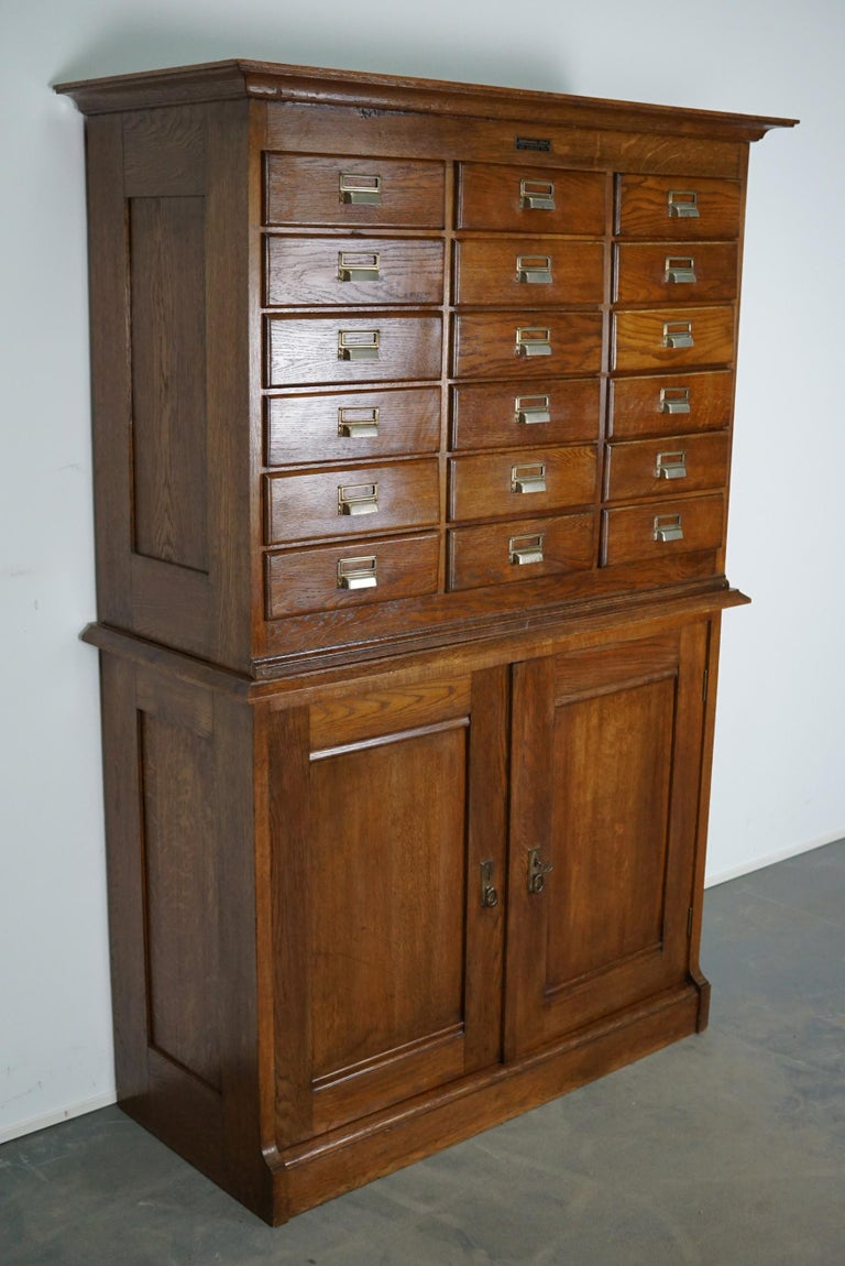 This apothecary cabinet was made circa 1930s in The Netherlands. It features 18 drawers with nice metal handles and two doors with a shelve behind it. The drawers can be locked with a central locking mechanism, most of the drawers lock but the