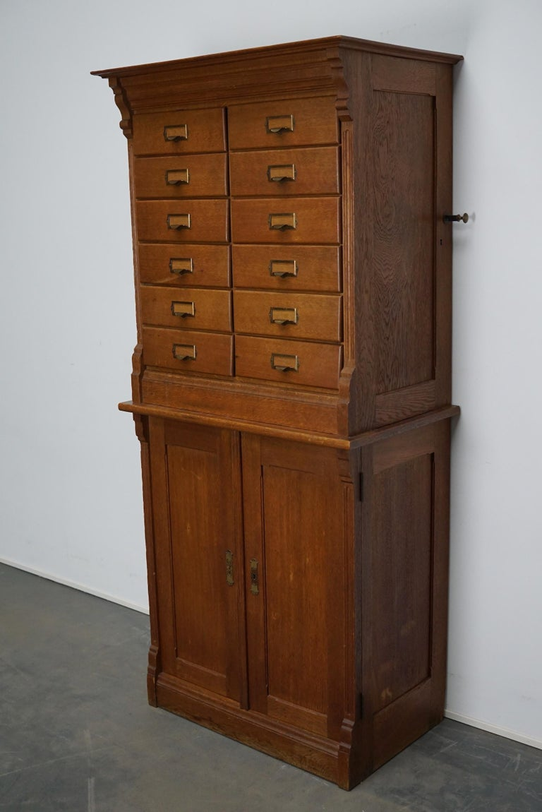 This apothecary cabinet was made circa 1930s in The Netherlands. It features 12 drawers with nice brass handles and two doors with shelves behind it. The drawers can be locked with a central locking mechanism, most of the drawers lock but the