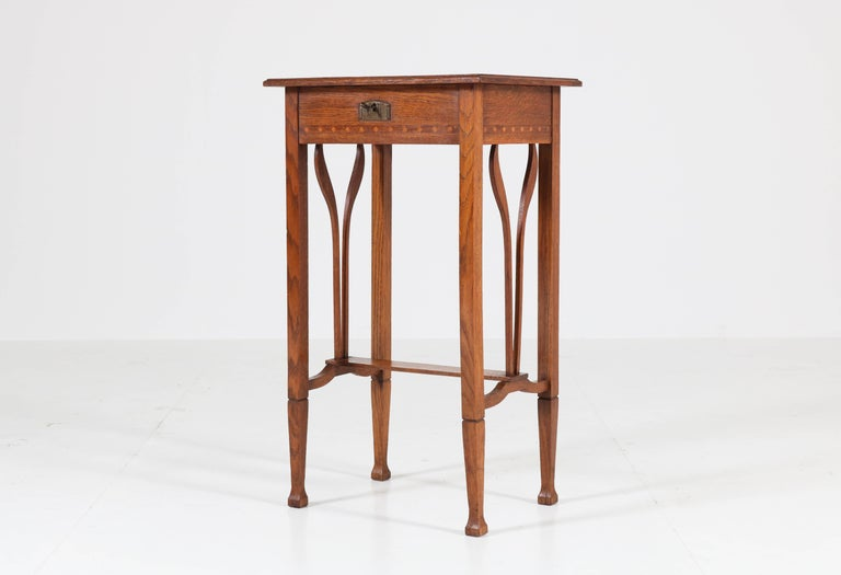 Elegant Art Nouveau Arts & Crafts sewing table. Striking Dutch design from the 1900s. Solid oak with original veneer inlay. Original lock and key and in good working order. In good original condition with minor wear consistent with age and