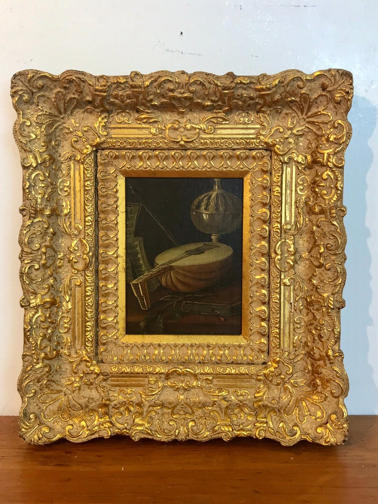 Dutch old master still life signed J. van Hoot, Exquisitely executed diminutive tablescape of a lute, book, flower and covered chalice, signed J. van Hoot lower right. In an elaborate carved giltwood frame