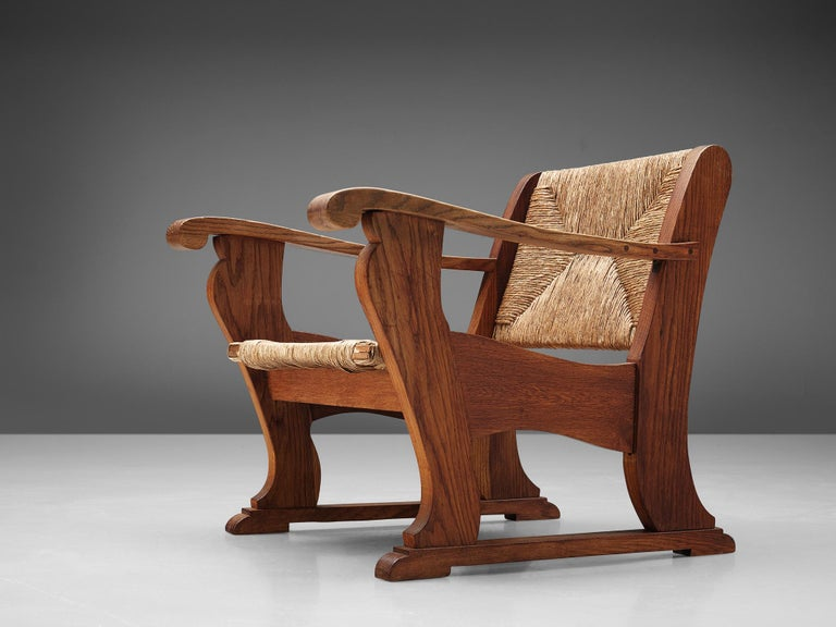 Wicker armchair, oak, Netherlands, 1930s.  This robust chair has a warm and inviting character. The legs continue in a horizontal base giving it a real grounded look and feeling.The tilted seating, executed in a centered woven cane pattern, and