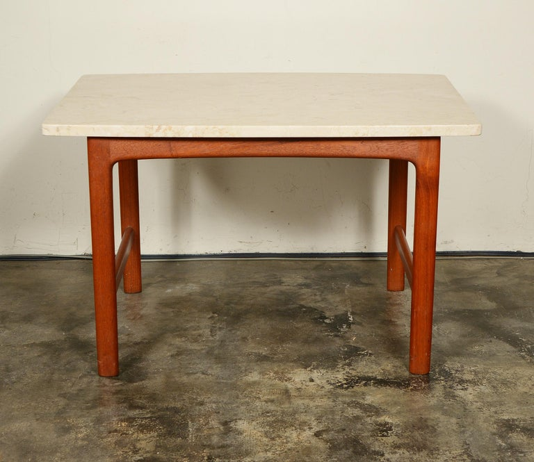 Teak side table with a travertine top designed by Folke Ohlsson for DUX. The contrast of the stone top with the simple teak base makes this table really pop over the all teak version. The table is in good condition. The travertine has a few small