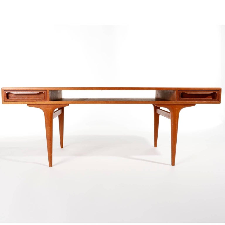 A Danish modern teak coffee table with a shelf and two drawers manufactured by Dyrlund, Denmark, in midcentury, circa 1960. The shelf below the top is perfect for magazines or books. The two drawers can be pulled through and pulled out on both