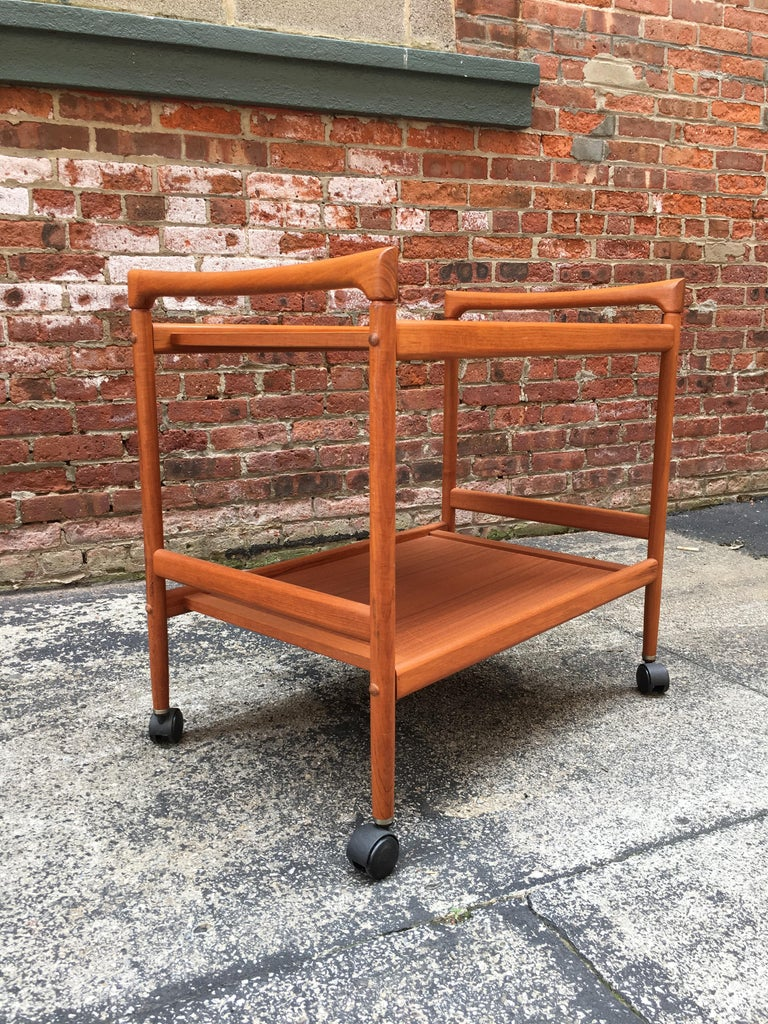 Dyrlund Danish teak rolling serving/media cart. The perfect Danish modern cart for a small flat screen TV, bric brac or rolling bar cart, circa 1970-1980. Black plastic casters. Very clean original condition. Signed on bottom.