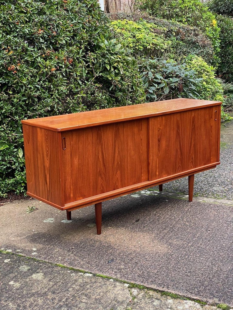 Dyrlund teak sideboard credenza midcentury Danish, circa 1970s.  Magnificent Mid-Century Modern Danish design Dyrlund teak sideboard Denmark circa 1970, the rectangular top over two cupboard with sliding doors and internal shelving, the right side