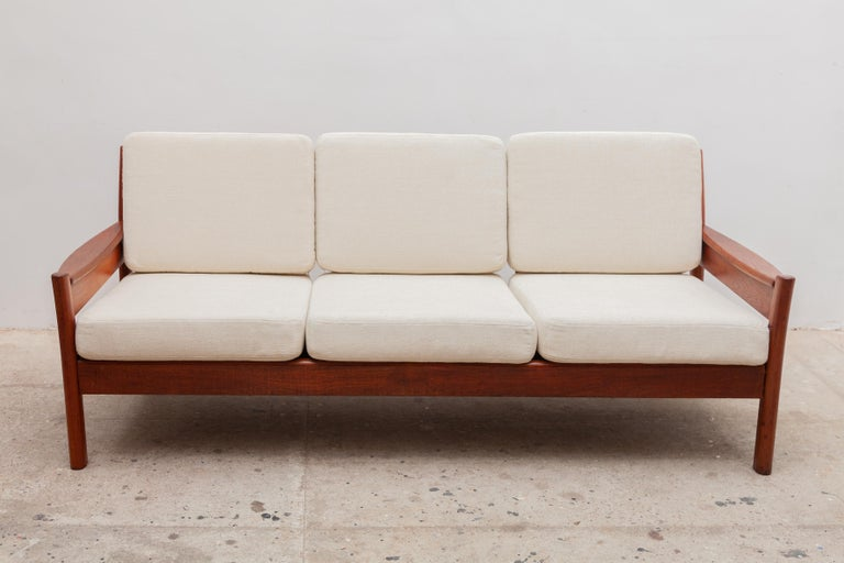 Vintage midcentury three-seat sofa by Dyrlund, Denmark. Elegant solid teak frame with new cream wool woven upholstery.