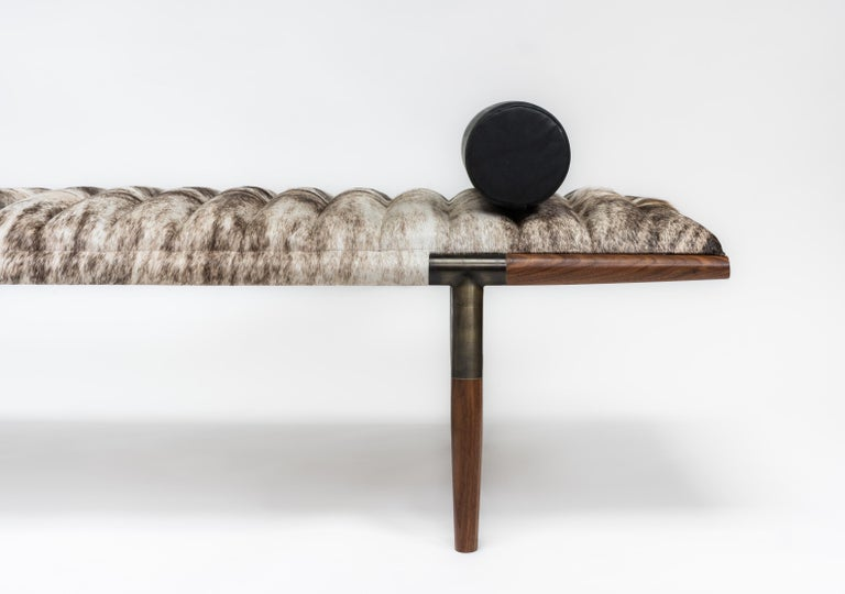 The EÆ daybed in ribbed grey Brazilian brindle hair-on-hide cushion with asymmetrically tapered oval black walnut legs and blackened brass frame. Matching or custom contrasting bolster included. This iconic design can be customized with different