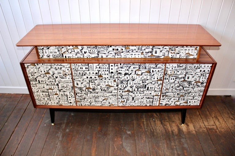 A beautifully made teak sideboard from 1958. Creatively decoupaged with a paper that featured in Piero Fornasetti's Milan residence. The sideboard has been restored. Sanded and oiled by hand. A wonderfully figured top section holding three drawers