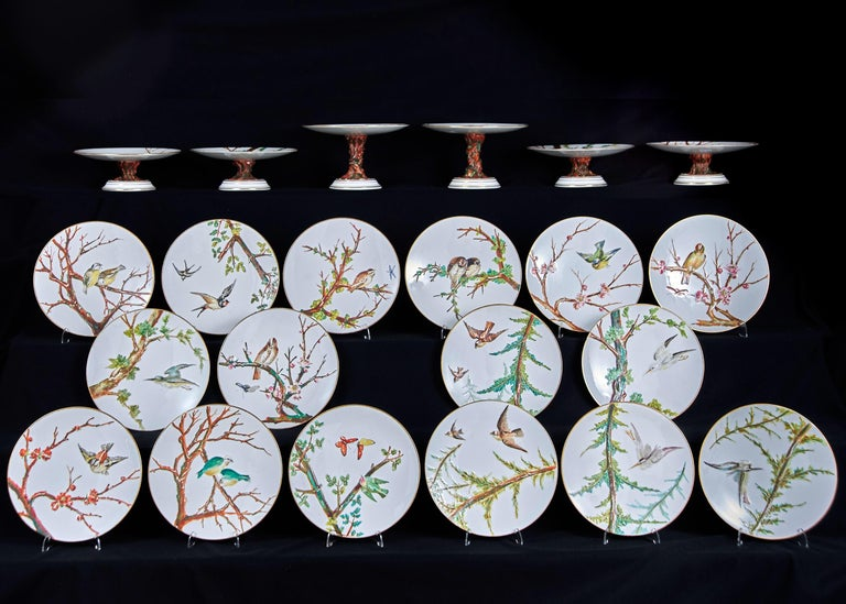 An E J D Bodley relief moulded bone China dessert service, C1880, enamelled with birds on branches in gilt dentil rim, the four low and two high stands on rustic foot, 23cm diameter, impressed mark and lozenge shaped podr mark for 29 January 1879,
