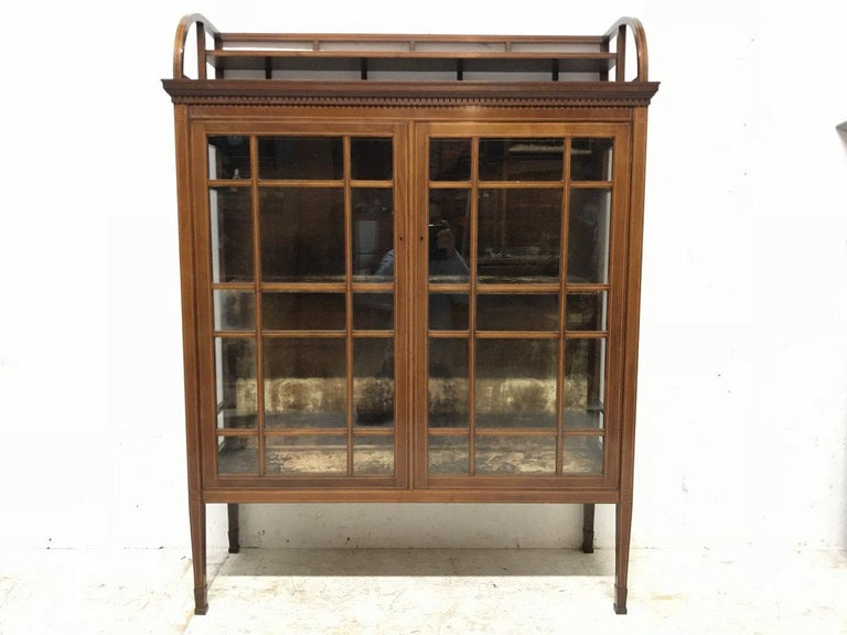 Edward William Godwin. Made by Collinson & Lock. A fine quality Anglo Japanese mahogany and astragal glazed cabinet with satinwood line inlay. The upper gallery with semi-circular sides supporting a half stepped shelf, with vertical staggered