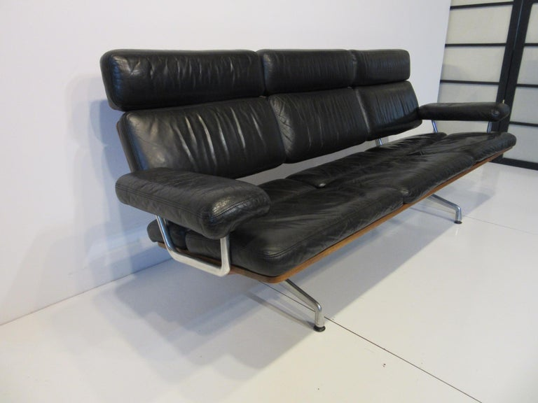 A rare and hard to find top of the line well crafted black leather soft pad sofa, with beautiful medium walnut back and cast aluminum legs. Model number 3473 one of the last designs put into production that was designed by the Charles Eames office.