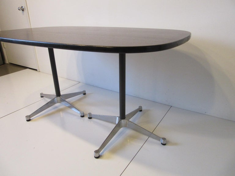 A nice sized medium ebony toned dining table with satin black edge having black pedestals attached to cast aluminum star bases with adjustable foot pads. Retains the labels designed by Ray and Charlies Eames for the Aluminum Group Collection