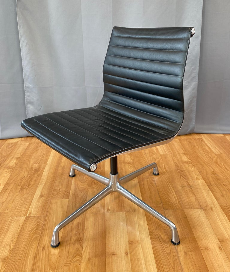 Offered here is a Eames aluminum group armless side chair.  Has an Aluminum frame and Black leather upholstery.  First designed in 1958, this one is circa 2000's.