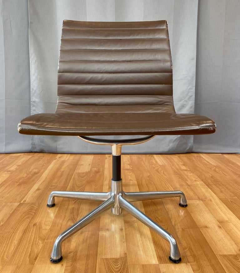 Offered here is a Eames aluminum group armless side chair.  Has an aluminum frame and brown leather upholstery.  First designed in 1958, this one is circa 2000's.