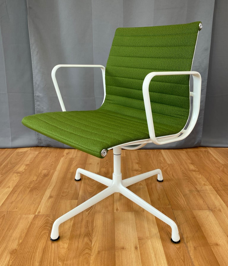 Offered here is a Eames aluminum group side chair, with arms.  Has a white frame. And light Olive green upholstery, that feels to be wool.  First designed in 1958, this one is circa 2000's.