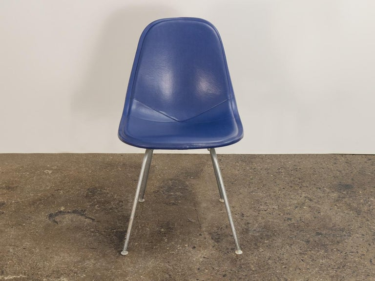 Classic wire chair with a blue seat pad, designed by Charles and Ray Eames for Herman Miller. Woven steel wire seat with original powder coated white finish. Blue Naugahyde cover is in great condition, soft and pliable to the touch. Shown mounted on