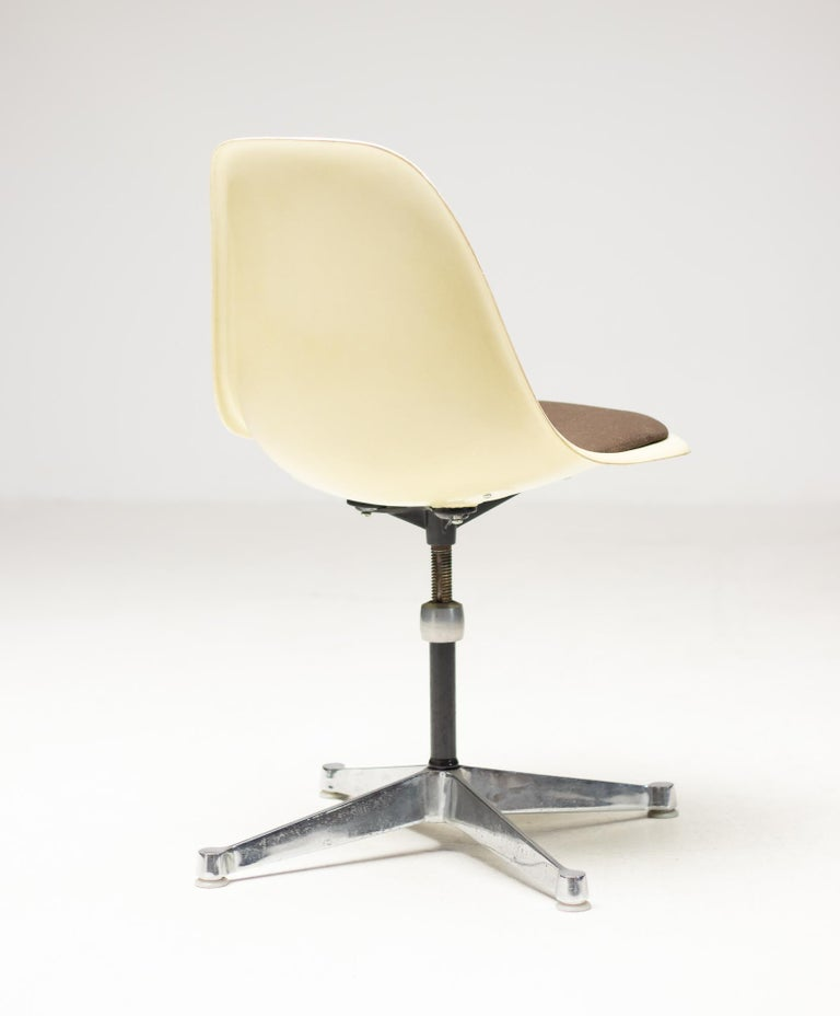 Swiveling parchment fiberglass side chair designed by Charles and Ray Eames for Herman Miller. Original seat pad with brown fabric, easy to reupholster when desired. Height adjustable, marked Herman Miller under the seat.