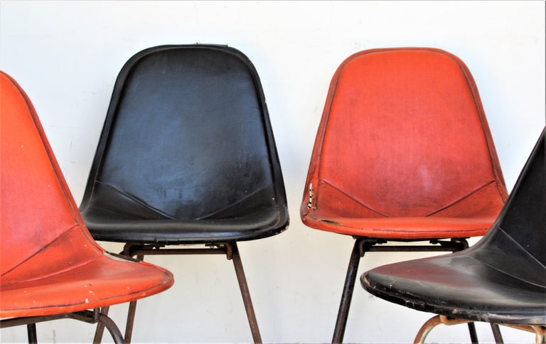 Set of four Eames DKX - 5 side side chairs for Herman Miller in original as found condition with rust to wire framework, rust to legs legs, wear and tear to period black and orange stitched vinyl seat covers, circa 1950. With all that said, these