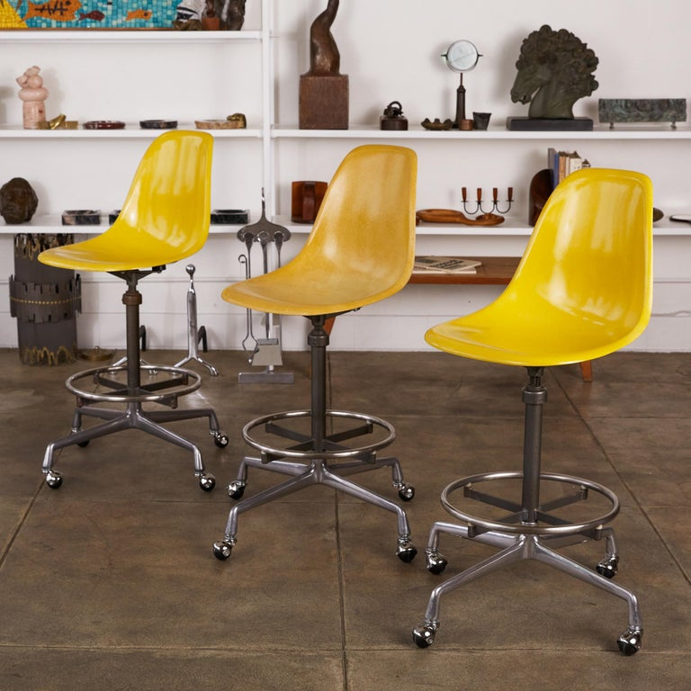 Set of three swiveling stools by Charles and Ray Eames for Herman Miller, circa 1975. The stools feature bright taxi cab yellow fiberglass shell seats that sit atop a height adjustable stem. The stools can be used for an office task chair or as a