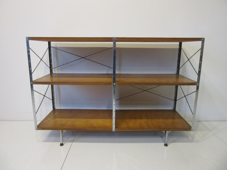 A vintage second series or generation Eames ESU 200- C storage unit with chrome coated steel L bracket frame and red divider panel. The top shelve is walnut ply while the two lower shelves are made of maple ply sitting on rounded legs marking it as