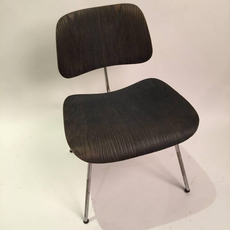 Black aniline DCM dining chairs by Charles and Ray Eames. These first edition chairs were produced by Evans manufacturing and distributed by Herman Miller. Chair has labels intact and original domes of silence glides. Excellent patina.