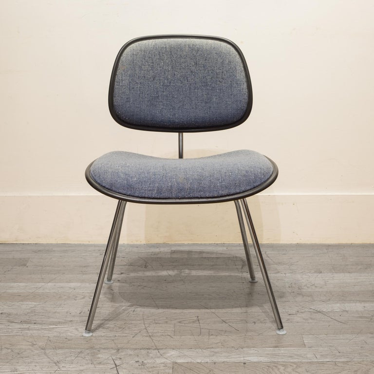 About  A EC-127 padded DCM chair by Charles Eames for Herman Miller. The padded seat and backrest are upholstered in light blue fabric with specs of dark blue and white. Grey vinyl piping with chrome plated frame and original Herman Miller
