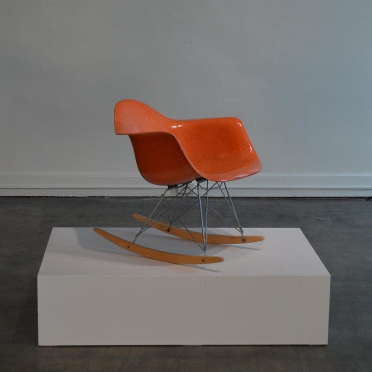 Ray and Charles Eames designed RAR rocking chair in red orange. Made, circa 1950s by Herman Miller of Zeeland, Michigan, US. Pristine example of the this icon of modern design. Molded fiberglass seat is in nearly unused condition, with almost no UV