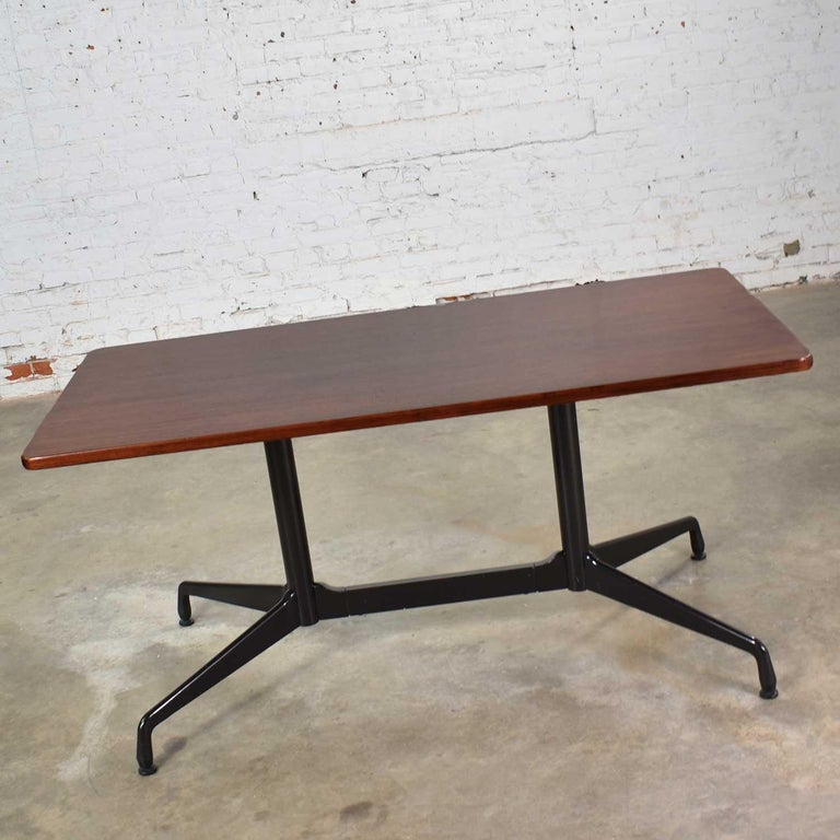 Handsome rectangular conference or dining table from the Aluminum Group designed by Charles and Ray Eames for Herman Miller. This one has a rosewood colored veneer top with black band and a black segmented double pedestal base. It is in wonderful