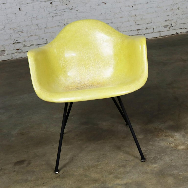 Awesome example of the Charles and Ray Eames LAX molded fiberglass arm shell chair for Herman Miller in one of the original colors, lemon yellow. This is an early chair made by Zenith with the rope edge, X-base, and checkerboard Zenith paper label.