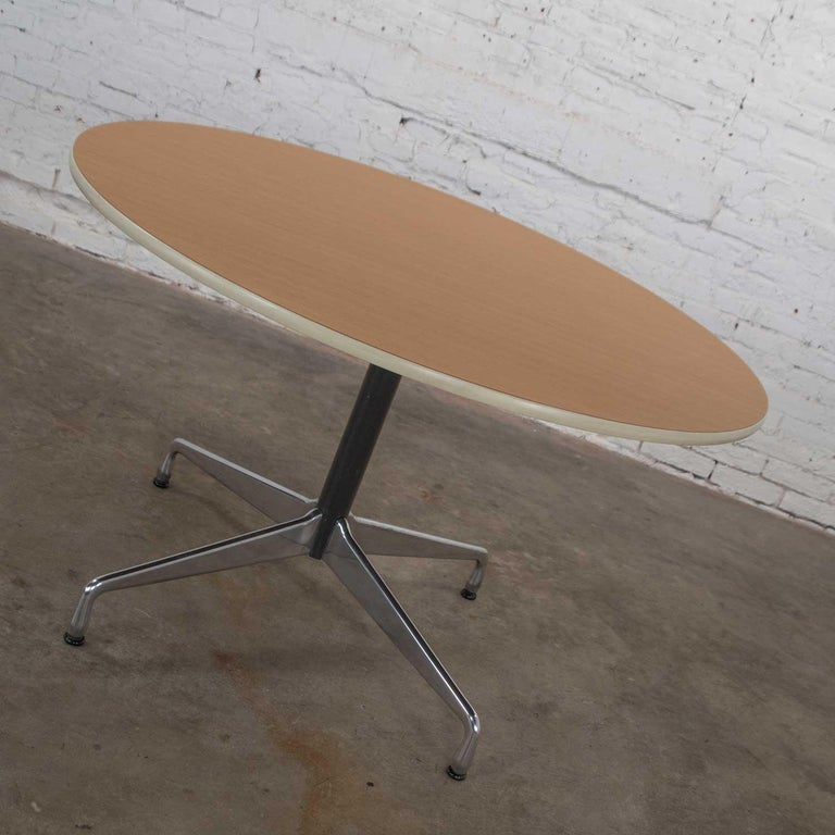 Renowned Eames Herman Miller round table with the universal base and a wood grain laminate top with off white edge trim, black painted shaft, and polished aluminum base. Wonderful vintage condition with no outstanding flaws that we have detected.