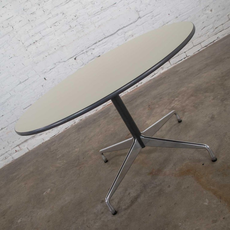 Fabulous Eames Herman Miller round table with the universal base and off-white laminate top with black edge trim and black painted shaft. Wonderful vintage condition. There is a very small nick on the edge of the white laminate but does not detract