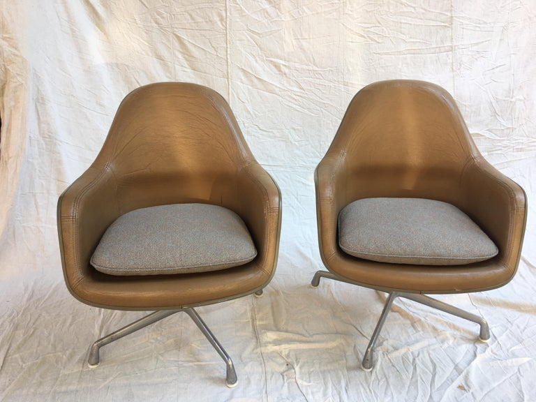Eames for Herman Miller high back leather lounge chairs. Uncommon pair with aluminum group bases and fiberglass seats. Leather is in good shape with 1 repair on each arm as seen in photos. Chair swivel and seat pads have been re-upholstered.