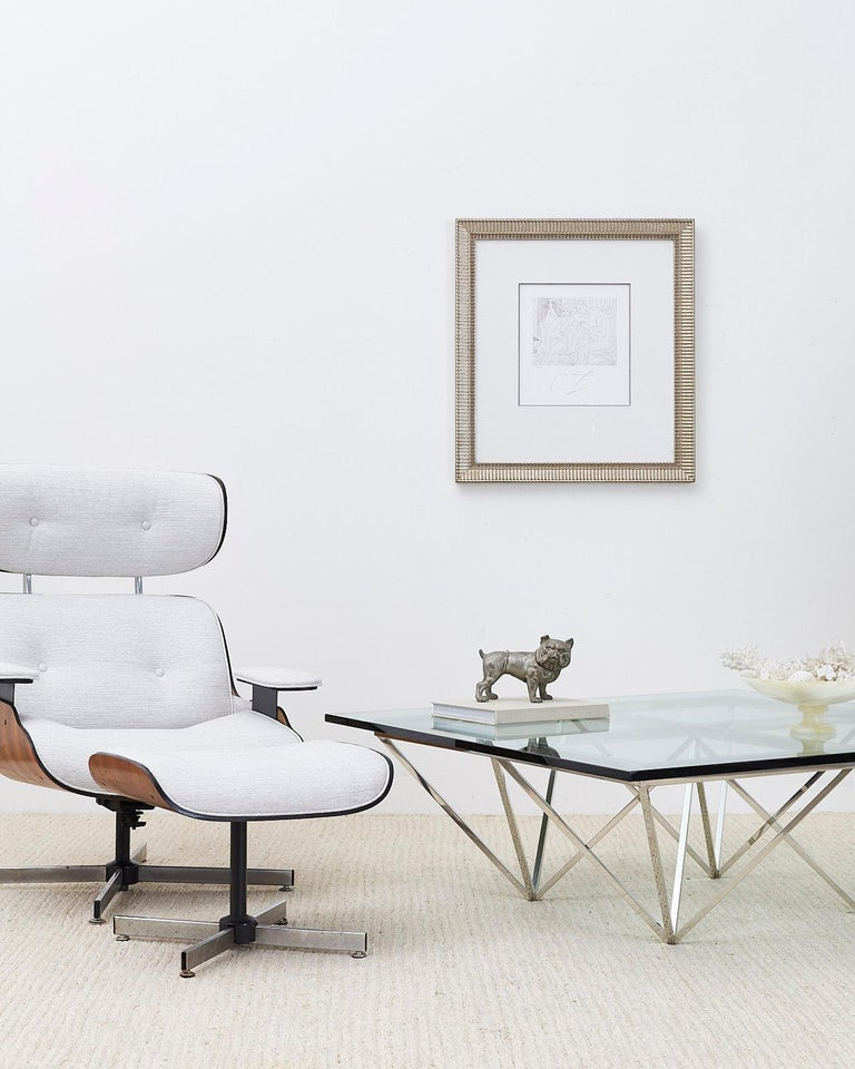 Stylish reupholstered swivel lounge chair and ottoman made in the manner and style of Charles and Ray Eames by Plycraft. Features a modern redux with a textured light gray fabric. Tufted seating surfaces with the iconic lounge chair profile. Ottoman