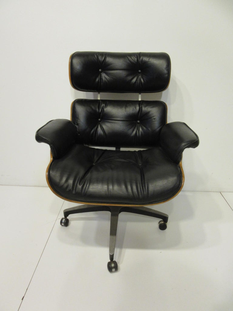 A super comfortable Eames styled black leather and walnut bodied rolling desk chair that looks like a Herman Miller 670 lounge chair. This chair has an adjustable height for any desk fit and bottom seat spring for comfort and a cast star aluminum