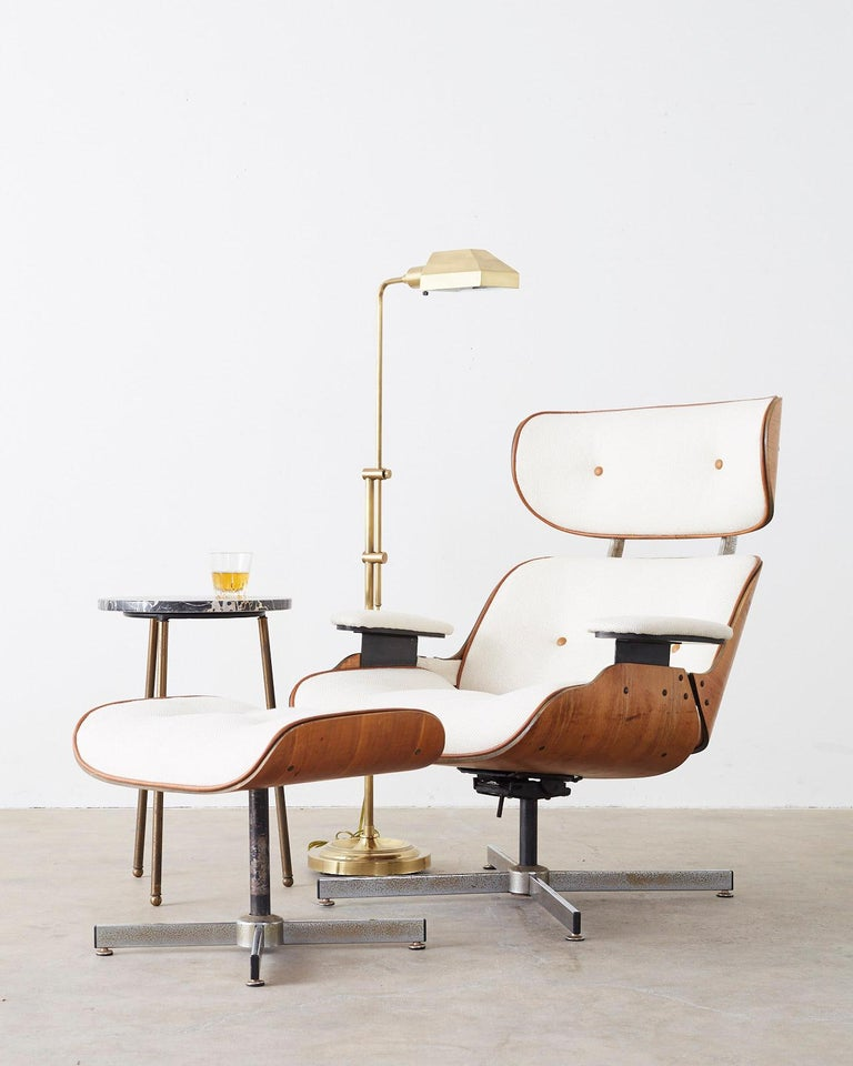 Chic reupholstered lounge chair and ottoman made in the manner and style of Charles and Ray Eames by Plycraft. Features a stylish chevron pattern fabric bordered with the original leather piping and buttons on the tufted seating surfaces. The